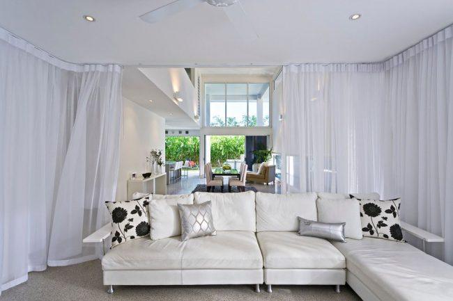 Des rideaux circulaires en tulle blanc séparent le coin salon et créent du confort