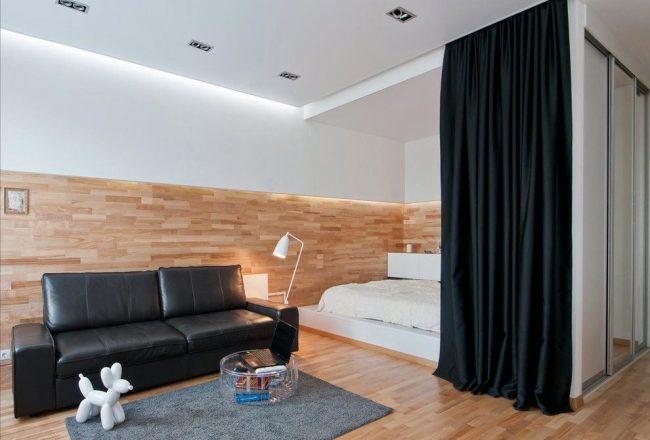 De beaux rideaux noirs en tissu épais séparent le lit du salon