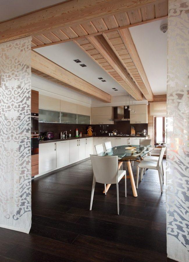 Des rideaux translucides à motif blanc remplacent les portes entre la cuisine et la pièce