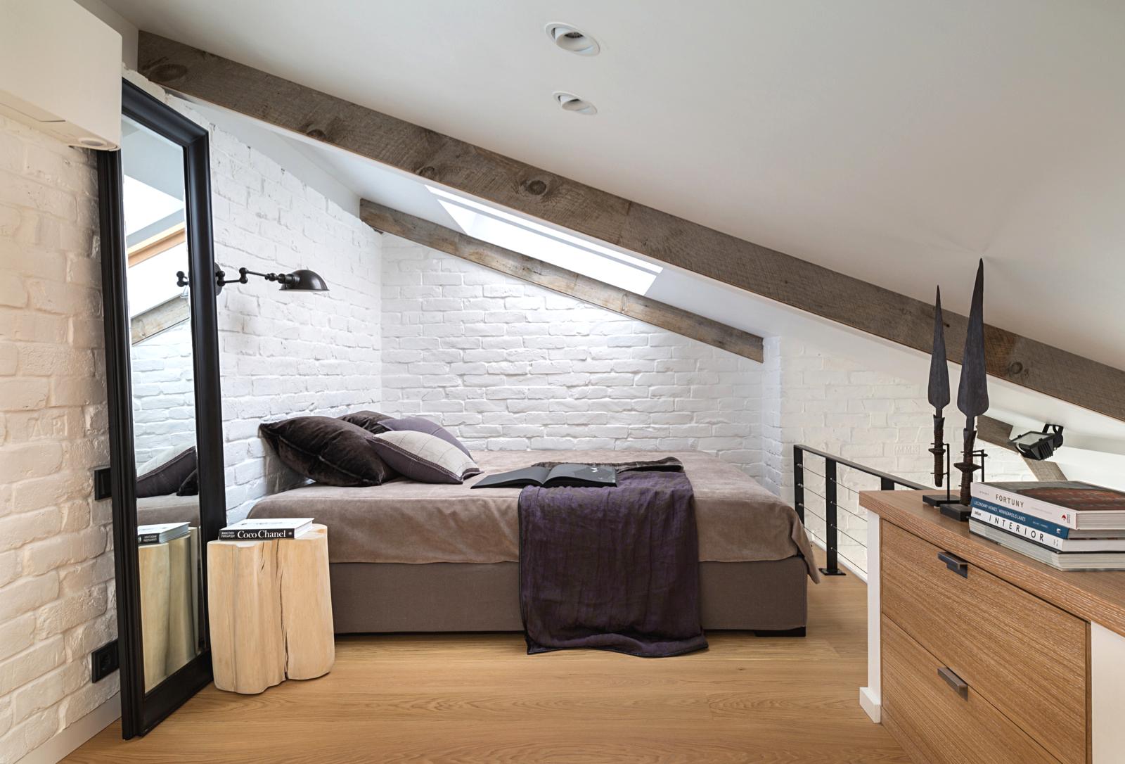 Chambre mansardée lumineuse avec une lampe de chevet montée sur le mur au-dessus du lit