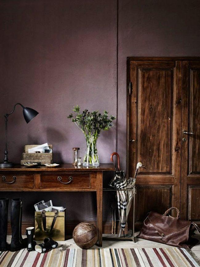 Un couloir très confortable dans une maison de campagne.  Le papier peint lilas se marie bien avec les meubles en bois massif naturel