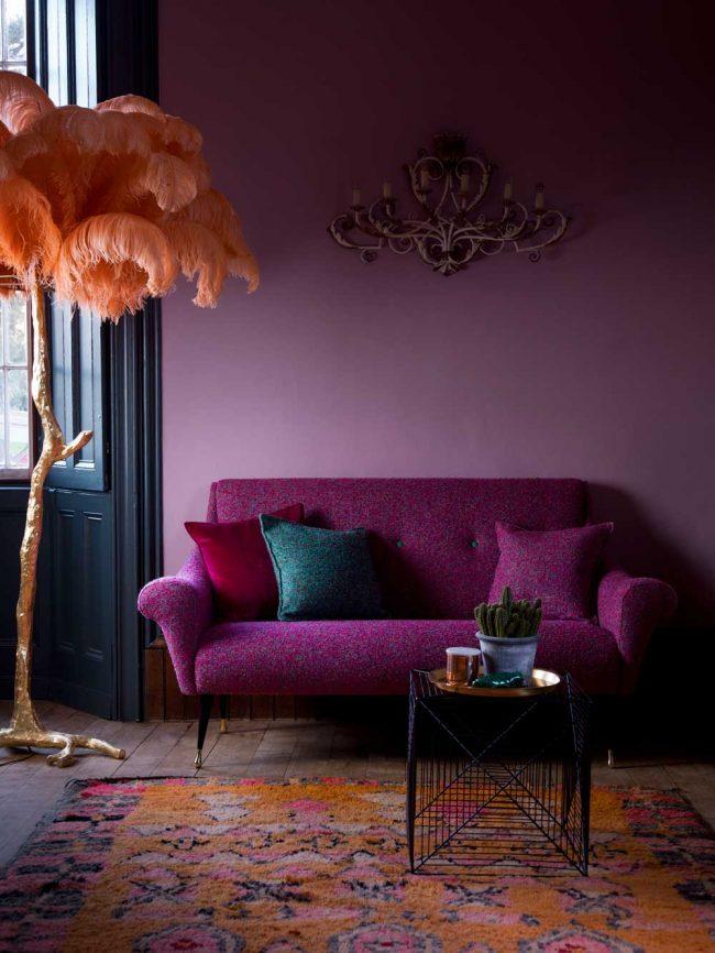 Salon confortable avec papier peint lilas aux couleurs pastel et accent lumineux sur un canapé confortable