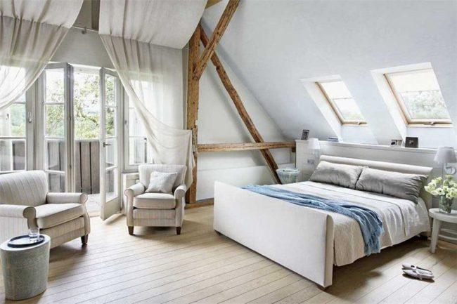 Beaux rideaux de toile suspendus au plafond dans la chambre mansardée