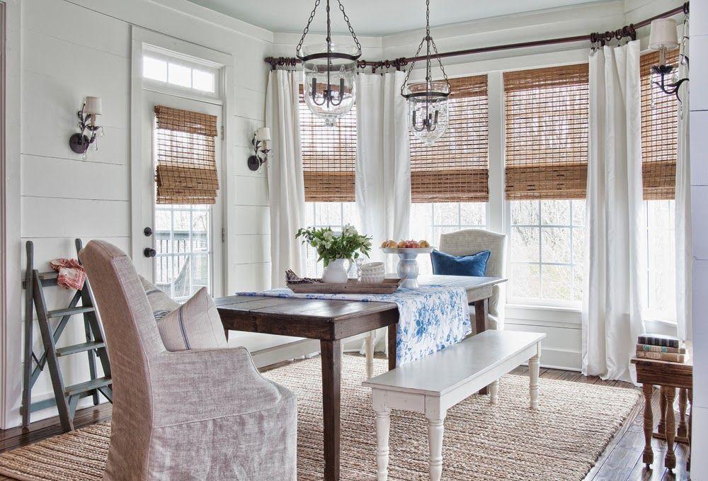 Les rouleaux en matériau naturel complètent le style général d'une cuisine rustique avec une baie vitrée