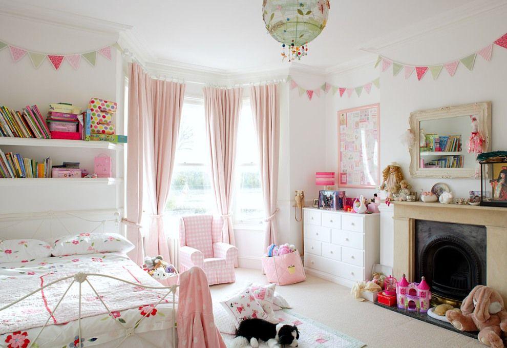 Les rideaux de la baie vitrée, de couleur rose tendre, ont fière allure dans la chambre des enfants
