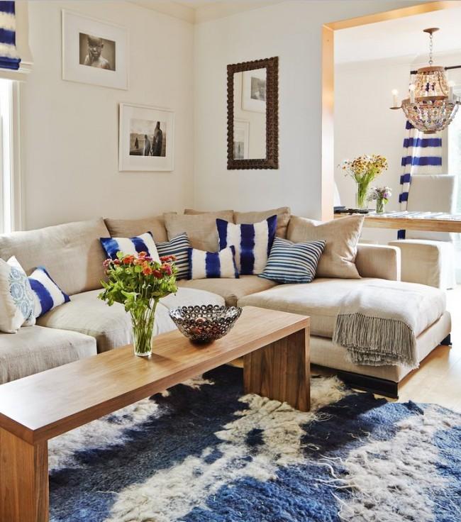 Canapé d'angle avec coussins bleus et blancs de la couleur des rideaux