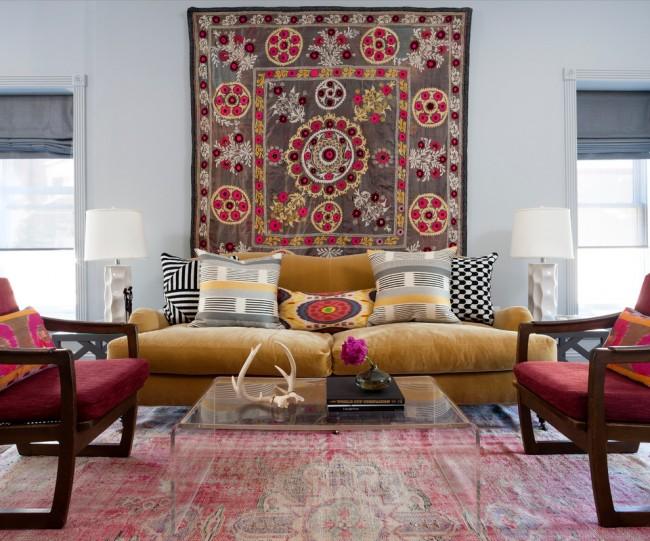 Tapis à l'intérieur du salon.  Un tapis en viscose qui ressemble à une détresse et un tapis avec un motif ethnique lumineux sur le mur constituent ensemble une excellente base pour un intérieur bohème-chic.