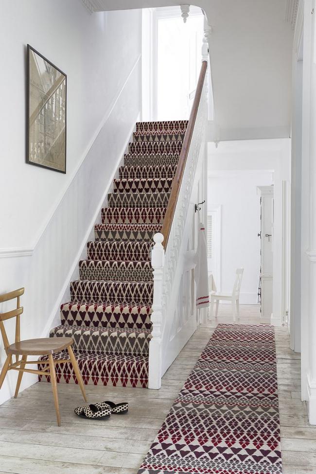 Des tapis avec le même imprimé décorent avec succès les escaliers et le couloir blanc comme neige