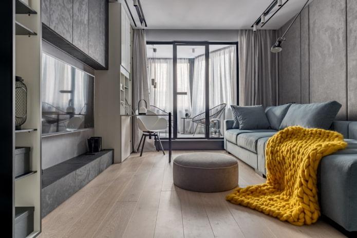 intérieur d'un salon gris avec une couverture lumineuse