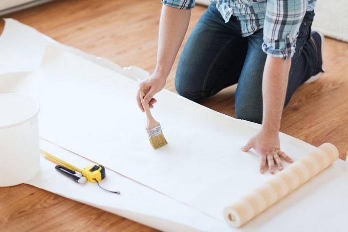 coller du papier peint, appliquer de la colle avec un pinceau