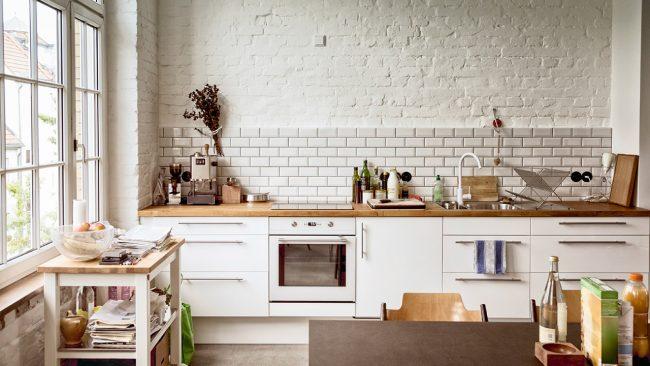 Cuisine blanche de style loft associée à un plan de travail en bois