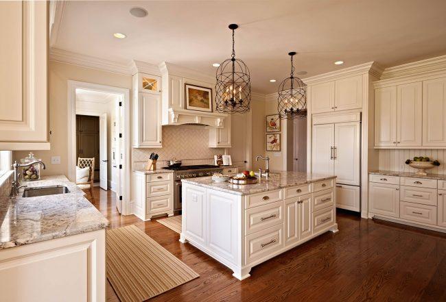 Intérieur de cuisine laconique et élégant de couleur ivoire.  Les comptoirs en marbre clair et les lampes vintage en fer forgé sont des accents caractéristiques pour une telle solution.