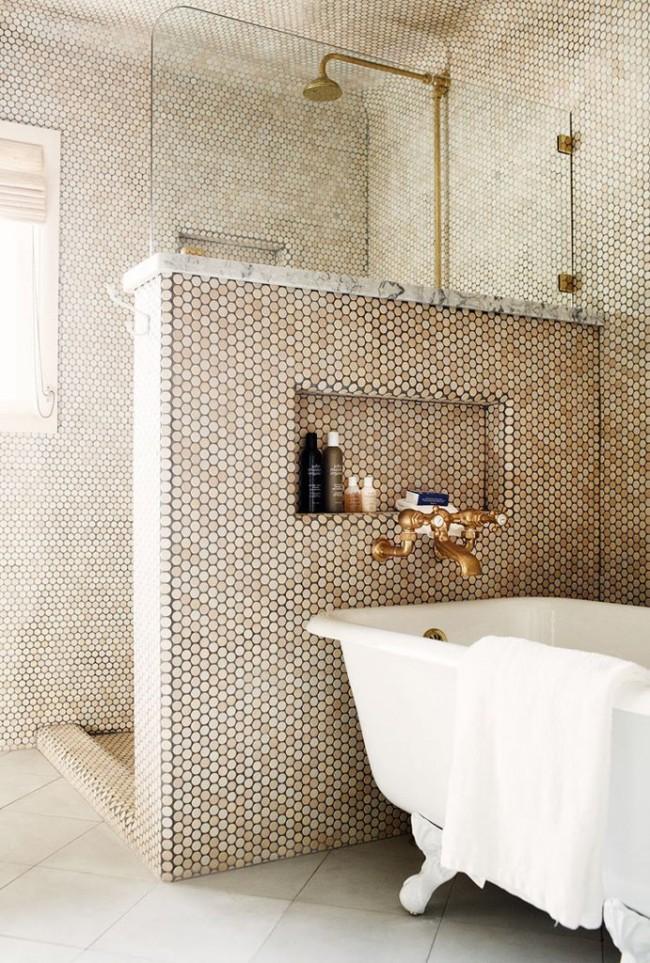 Une chambre en mosaïque dorée avec une cloison basse entre la salle de bain et la douche