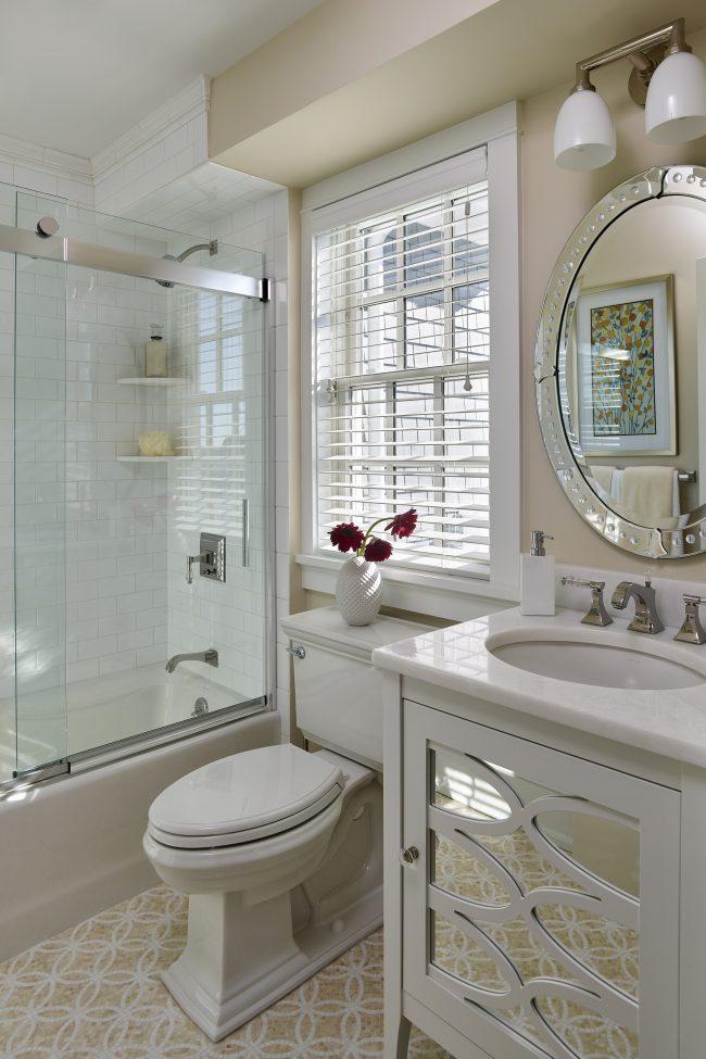 Rideau coulissant en verre solidement fixé avec des plaques métalliques dans une salle de bain lumineuse