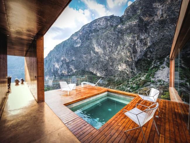 Terrasse luxueuse construite au-dessus de la piscine.  Pour que rien ne gêne l'image de la vue sur la montagne, le garde-corps de cette terrasse est en verre
