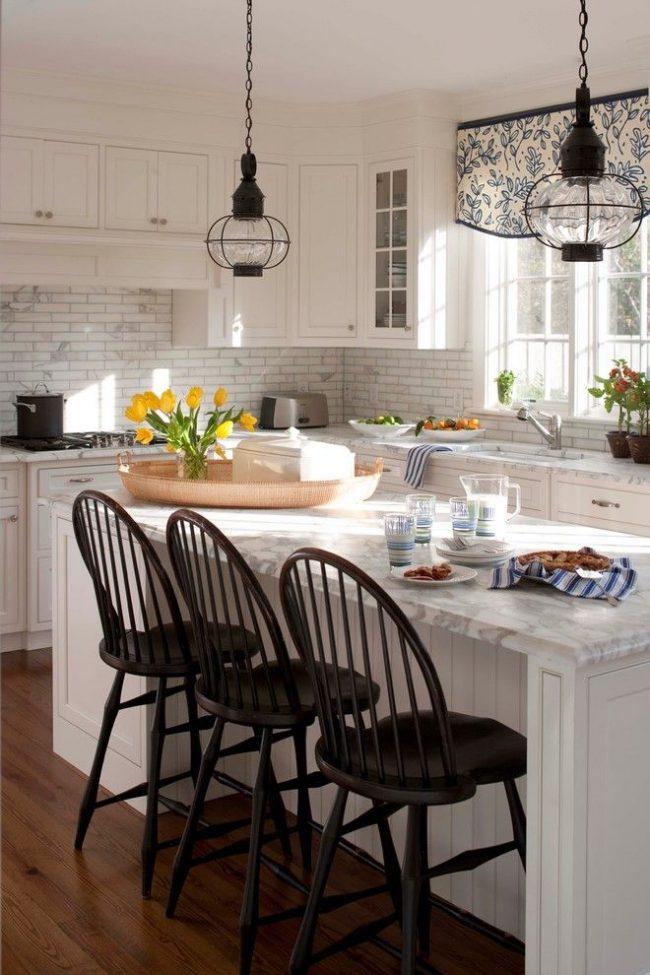 Rideaux courts pour la cuisine comme accent qui se distingue par un simple ornement floral, en accord avec l'abondance de fleurs fraîches sur les surfaces, le travail et la salle à manger