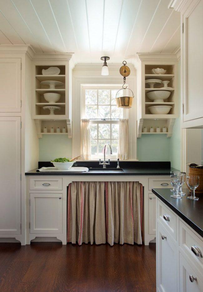 Une cuisine de style plage avec une palette de couleurs distinctive : un tablier de cuisine bleu doux, des façades de casque blanches, des rideaux de sable clair raccourcis aux fenêtres, etc.