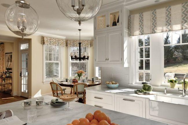 Espace cuisine de travail en combinaison avec des rideaux occultants raccourcis qui servent de rôle décoratif.  Coin repas - rideaux imprimés coupés et stores fonctionnels