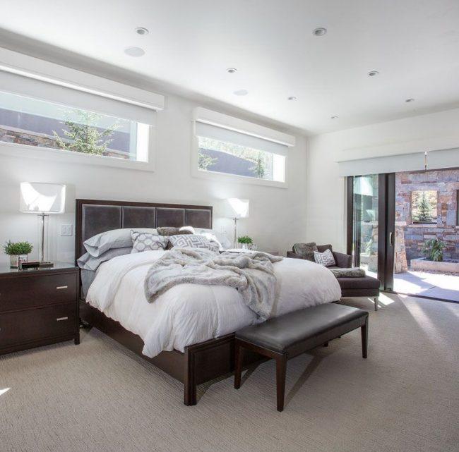 L'installation d'un lit avec une tête de lit à la fenêtre peut être prévue même pendant la phase de construction.  Pour ce faire, vous devez choisir une pièce d'angle et installer des fenêtres étroites aussi près que possible du plafond.
