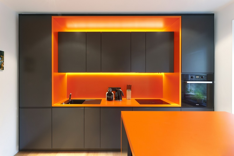 Les systèmes de hotte, les tabliers et les façades rétroéclairées seront un excellent ajout au style de cuisine orange et noir.