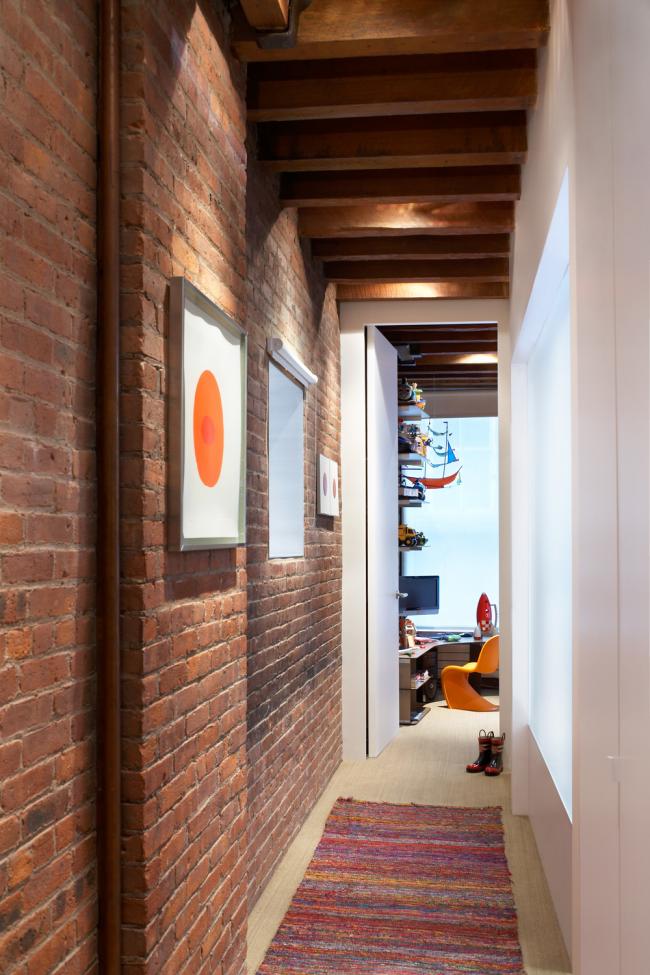 Éclairage ponctuel uniforme dans un long couloir avec des murs en briques et des poutres en bois très atmosphériques au plafond