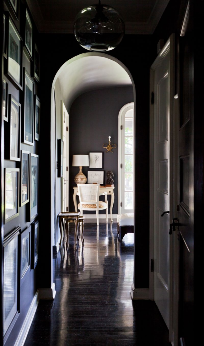 Une solution audacieuse pour la conception d'un couloir étroit avec un haut plafond consiste à le décorer dans des couleurs sombres, où le centre d'attention sera un grand abat-jour en verre noir