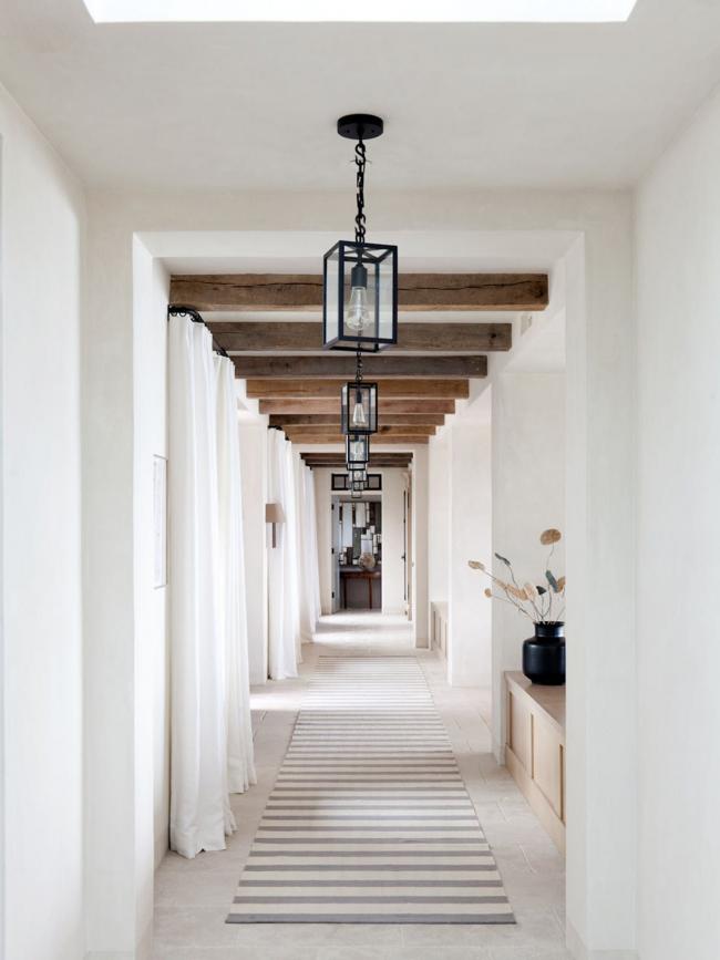 Un couloir étroit aux couleurs claires avec une rangée de lampes qui éclairent uniformément toute la pièce