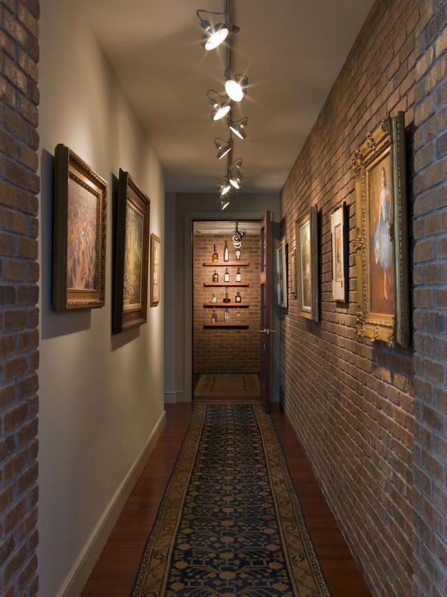 Une solution inhabituelle pour un couloir étroit d'un appartement - des murs décorés de briques, qui sont soulignés par la conception d'éclairage d'origine