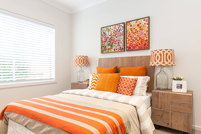 L'ambiance lumineuse et ensoleillée de la chambre est organiquement soulignée par des tons pêche, terre cuite et orange.