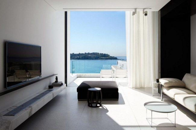 Une chambre spacieuse avec un minimum de détails : une étagère avec une télévision, une grande fenêtre, un canapé, une table basse