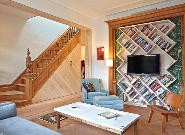 Solution design pour le salon d'une maison de campagne : une étagère TV est placée dans une découpe avec des étagères diagonales pour les livres