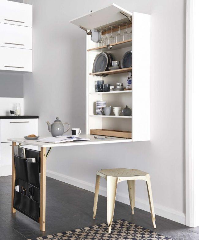 Table transformable 3 en 1, comprenant les fonctions suivantes : coin repas, étagères pour ranger la vaisselle et poches pour ranger les petits objets de cuisine