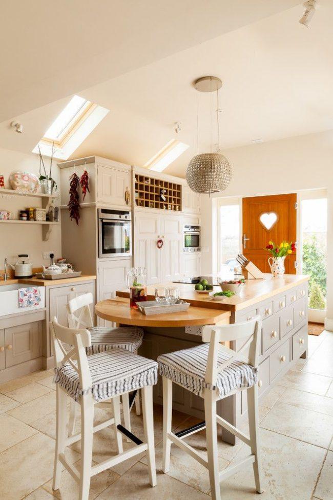Cuisine rustique : beaucoup de lumière, des meubles en bois et une porte avec un cœur de fenêtre, une décoration textile de chaises hautes et de nombreux détails intérieurs mignons.  Petite table avec support - modification d'un coin repas compact