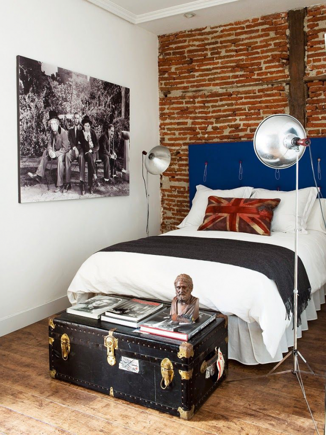 Un coffre recouvert de cuir avec du matériel doré complète l'intérieur brutal d'une chambre d'adolescent