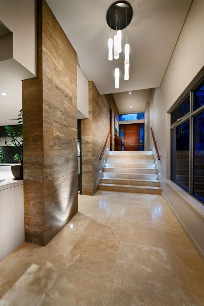 Hall d'entrée élégant avec des murs carrelés de carreaux de pierre et éclairé par le bas