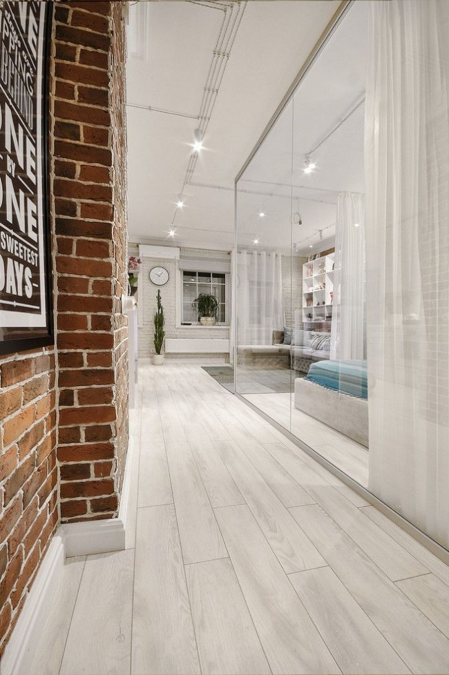 Le mur de briques brunes dans le couloir est magnifiquement combiné avec le verre et la couleur blanche de l'intérieur principal.  Certains fabricants appellent ces variétés pour imiter la maçonnerie