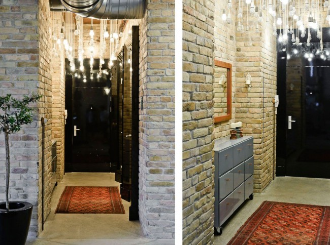 Hall d'entrée étroit d'un appartement standard avec des murs en briques claires et un éclairage zénithal spectaculaire