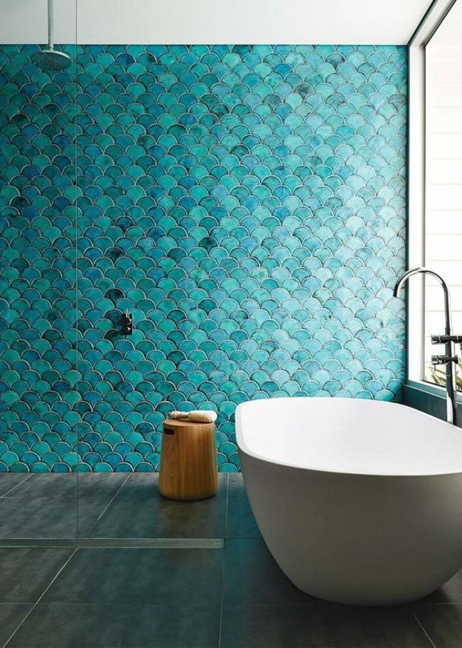 Une baignoire en céramique sur fond de carreaux turquoise est très impressionnante