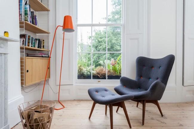 Intérieur laconique et typiquement scandinave : luminosité maximale, sol naturel, fenêtre en bois, mobilier minimaliste et accents lumineux sous forme d'accessoires
