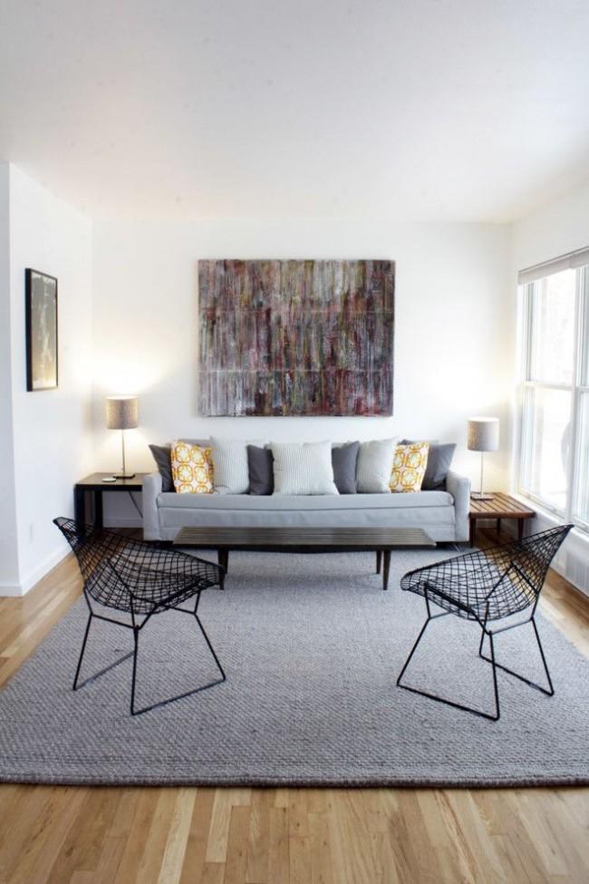 Fauteuils Frame, coussins, panneaux abstraits au-dessus du canapé - des éléments qui contrastent avec la palette de couleurs unies du salon