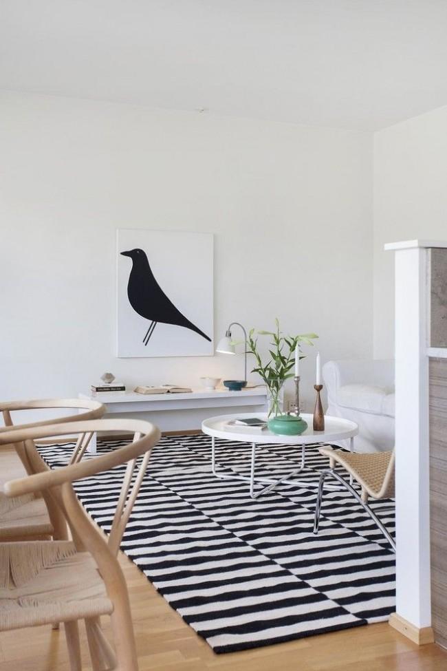 Une palette de couleurs assaisonnées dans un intérieur scandinave, combinée avec des chaises en osier, des accessoires et des beaux-arts modernes