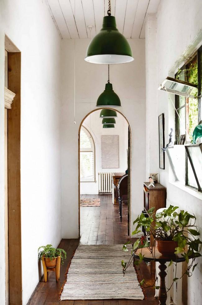 Un couloir étroit mettant l'accent sur de grandes nuances vertes et des plantes vivantes crée une atmosphère chaleureuse
