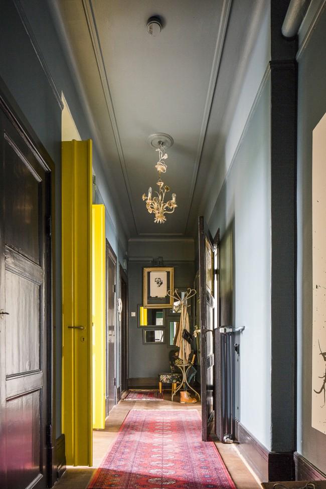 Conception unique d'un couloir étroit avec des accents sur des portes jaune vif et des revêtements muraux pratiques et faciles à nettoyer