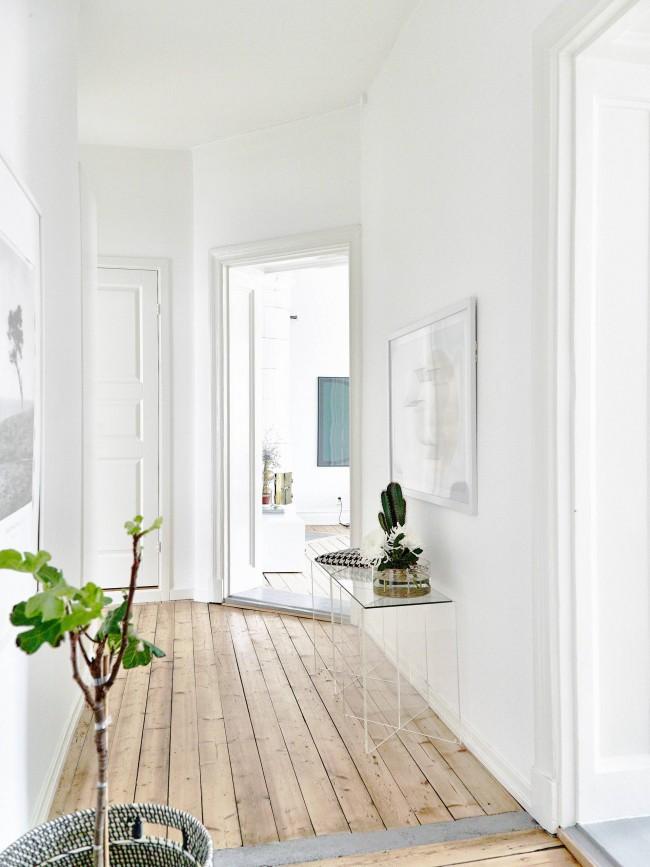 Petit couloir aux tons blancs avec parquet clair.  L'espace dans de telles conditions augmente visuellement parfois.