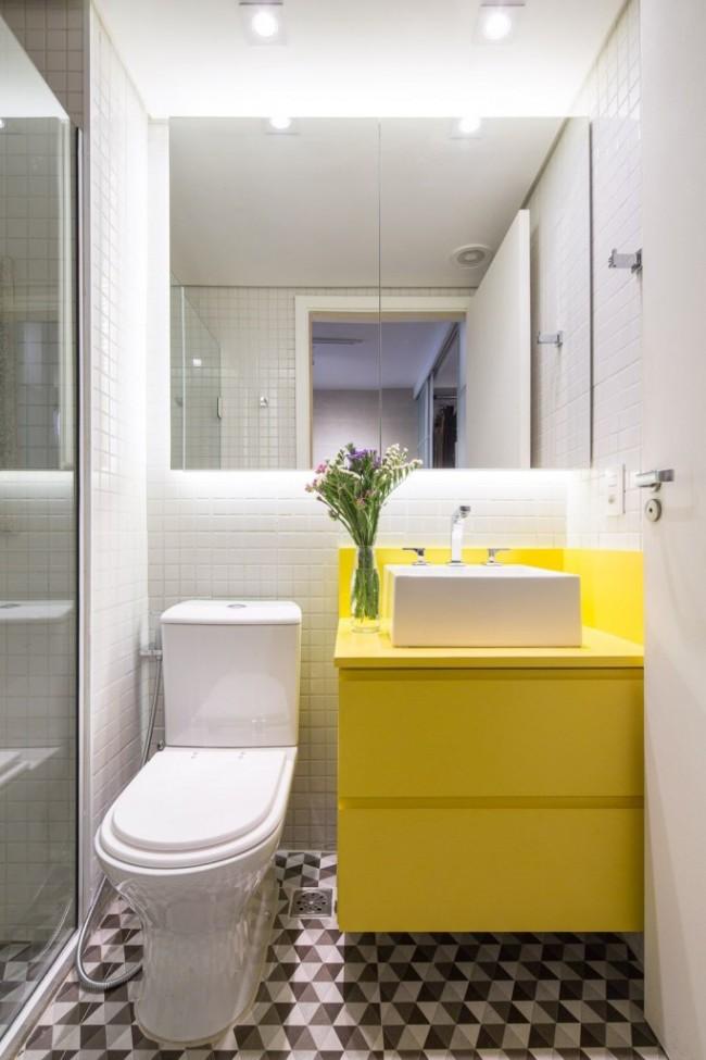 Salle de bain lumineuse aux accents lumineux.  Le petit motif géométrique sur le sol cache les vraies limites de l'espace