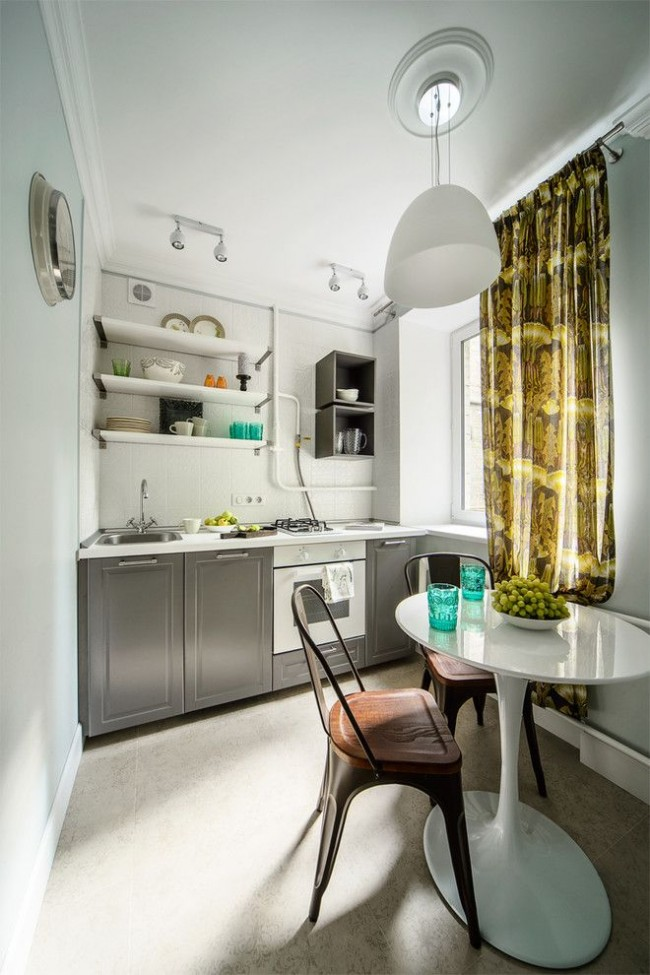 Petite cuisine avec une table à manger ronde miniature et deux chaises