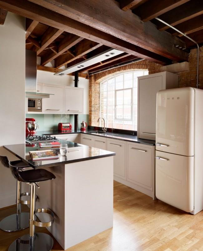 Appareils électroménagers intégrés dans la zone de travail, et le réfrigérateur est un séparateur entre la cuisine et la pièce