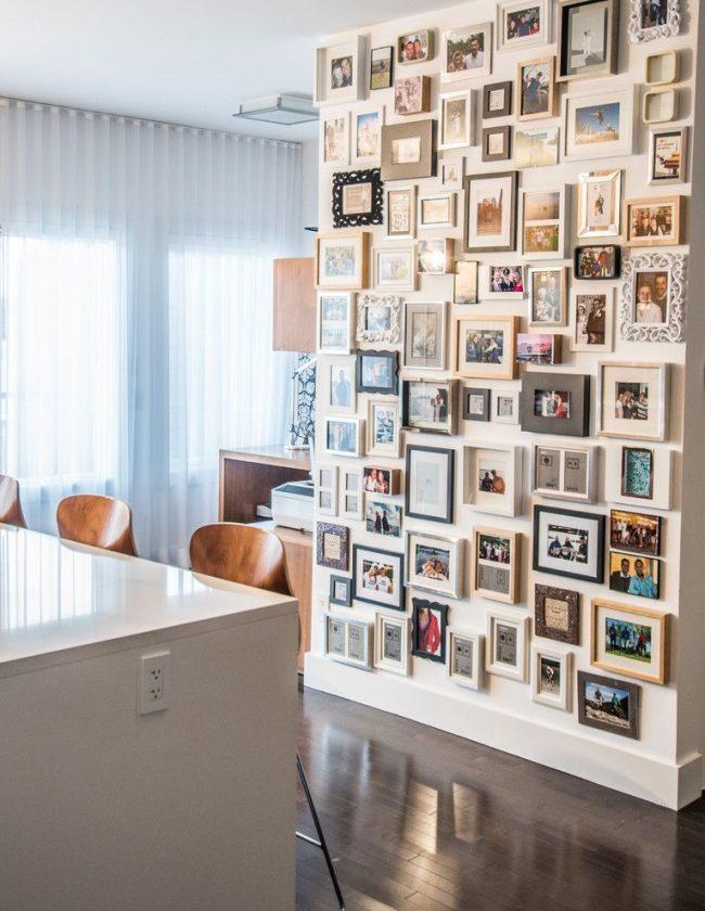 Collage de photos dans des cadres de différentes formes, couleurs et décors.  L'agencement original, qui occupe tout un mur de la cuisine-studio, forme un tout