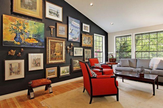 Salon avec une exposition de peintures réalisées avec différentes techniques et différents matériaux.  La décoration des tableaux est variée : cadres décorés de couleur or, cadres ordinaires en bois naturel, cadres noirs standards, etc.