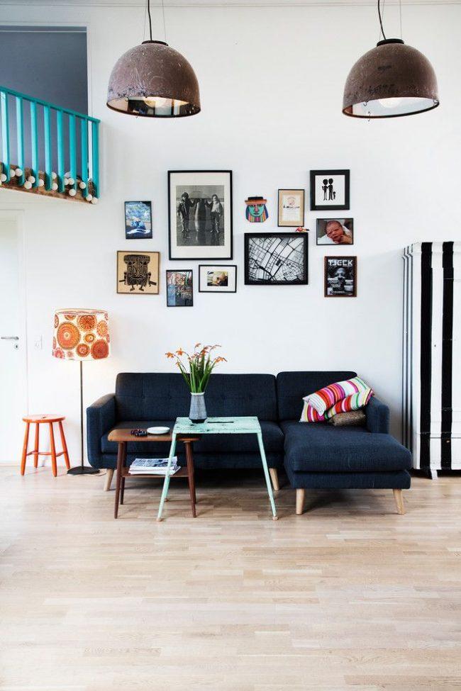 Un salon éclectique avec une sélection originale de photos dans des cadres sombres de différentes formes et épaisseurs